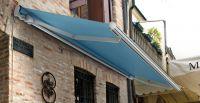 Offene-Gelenkarmmarkise-blau-Steinmauer