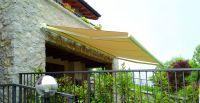 Kassettenmarkise-gelb-Steinmauer-Balkon
